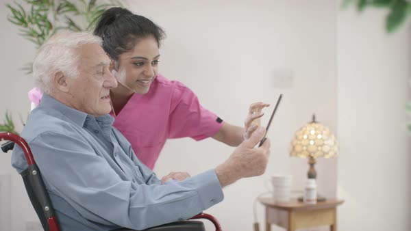 Caring young home support nurse helping elderly gentleman to use a computer tablet. Royalty-free stock video