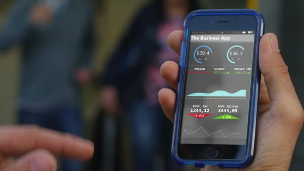 Close-up of hand holding a smartphone outdoors, a business application is displayed on the screen. Royalty-free stock video