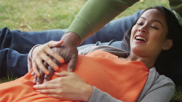 Happy couple expecting a baby relaxing in the park with hands on tummy. Royalty-free stock video
