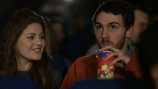 Cinema audience watching a movie with focus on happy young dating couple. Royalty-free stock video