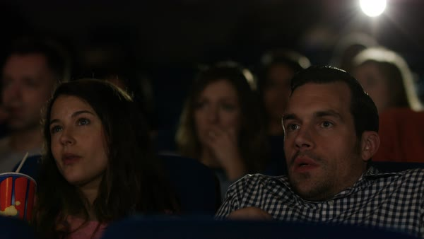 Couple watching film in crowded movie theatre, man spills popcorn as he reacts to the action on screen. Royalty-free stock video