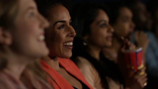 Happy young female friends watching a film in movie theatre. Royalty-free stock video