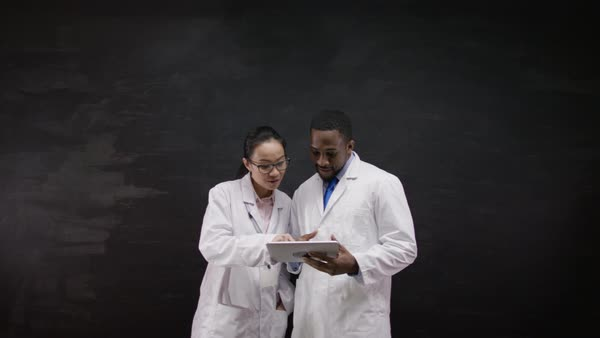 Portrait of doctors in white coats, standing in front of blank blackboard with a tablet computer. Royalty-free stock video