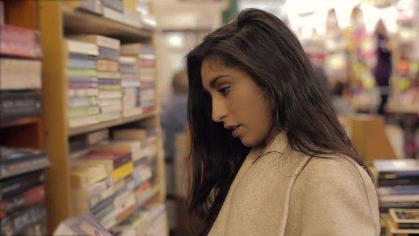 Medium close-up of a woman looking inside a book in a bookstore Royalty-free stock video