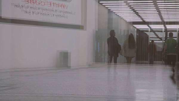 Reflection of commuters walking through a modern underpass in the city of London in the daytime Royalty-free stock video