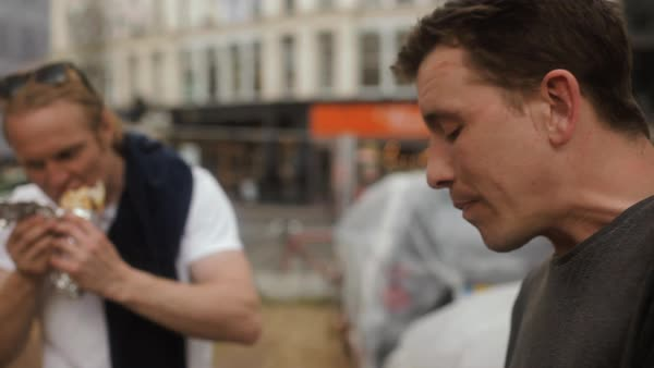 Close-up shot of men eating on a street Royalty-free stock video