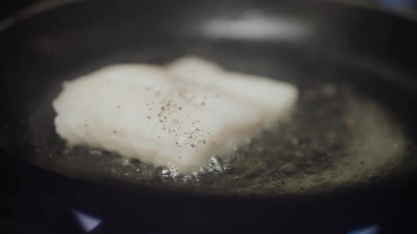 Hand-held shot of a fish fillet in a frying pan Royalty-free stock video