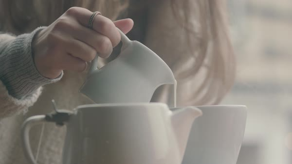Hand-held shot of a woman pouring milk into a mug Royalty-free stock video