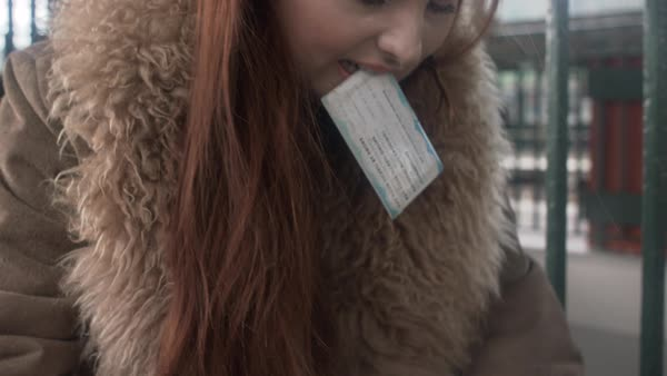 Hand-held shot of a woman packing with a train ticket in her mouth Royalty-free stock video