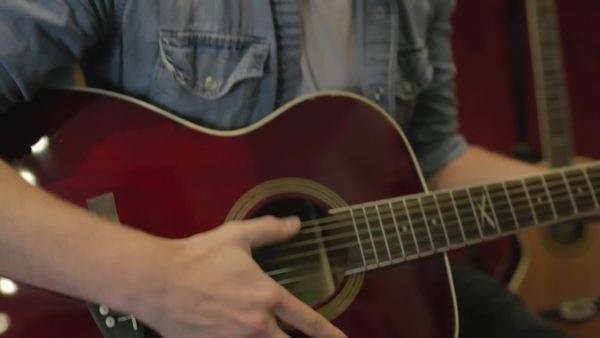 Medium close-up shot of a man playing the acoustic guitar Royalty-free stock video