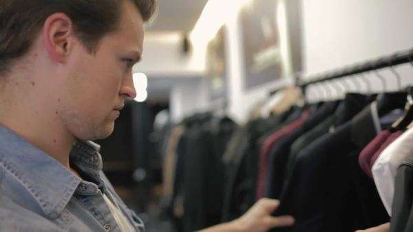 Medium close-up shot of a man browsing clothes in a store Royalty-free stock video