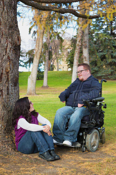 Disabled husband talking with his wife in a park in autumn; Edmonton, Alberta, Canada Royalty-free stock photo