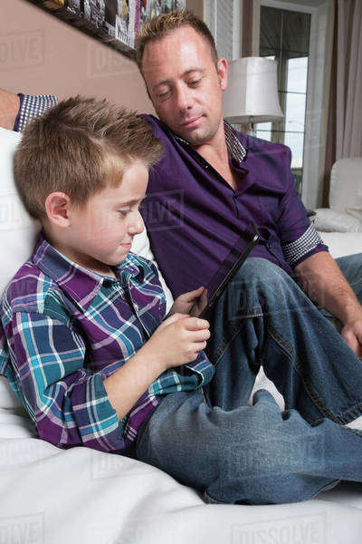 Father and son spending time together looking at tablet; Spruce Grove, Alberta, Canada Royalty-free stock photo