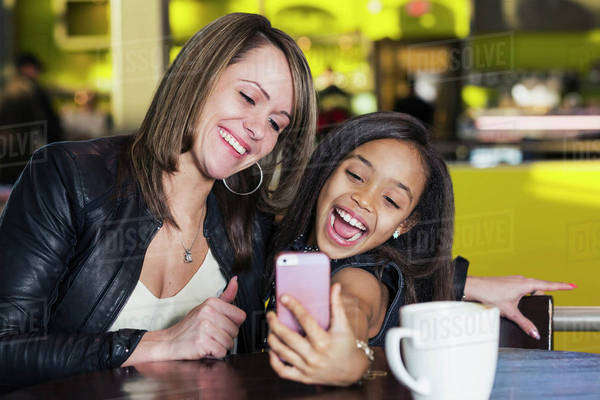 Young mother and her daughter in a cafe looking at a smart phone and taking a selfie while taking a break from shopping; St. Albert, Alberta, Canada Royalty-free stock photo