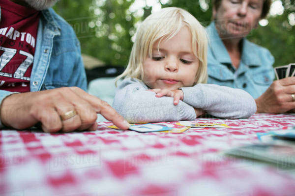 Grandparents teaching a young granddaughter how to play a card game; Peachland, British Columbia, Canada Royalty-free stock photo