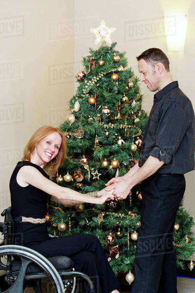 Couple decorating a Christmas tree together with wife in a wheelchair; Edmonton, Alberta, Canada Royalty-free stock photo
