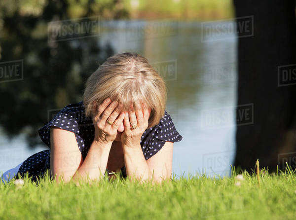 A woman on the grass in a park with her face buried in her hands; Edmonton, Alberta, Canada Royalty-free stock photo