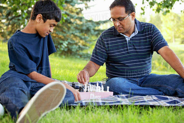 Father and son spending quality time together outdoors playing chess; Edmonton, Alberta, Canada Royalty-free stock photo