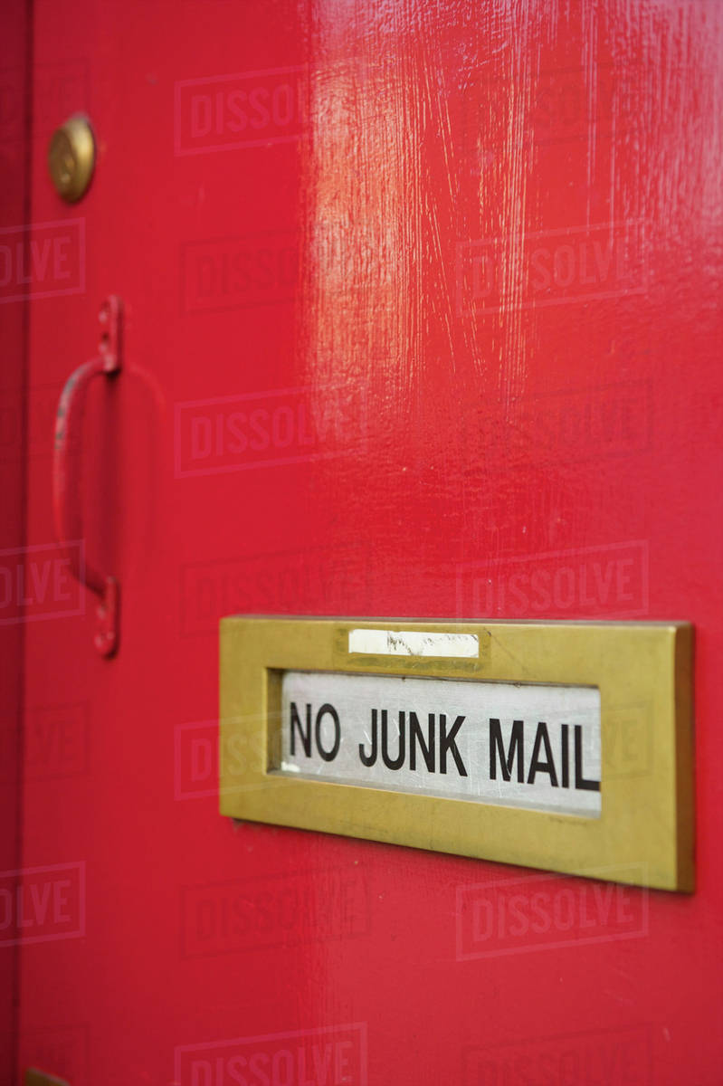 A Sign On A Mail Slot On A Red Door Saying No Junk Mail; London, England