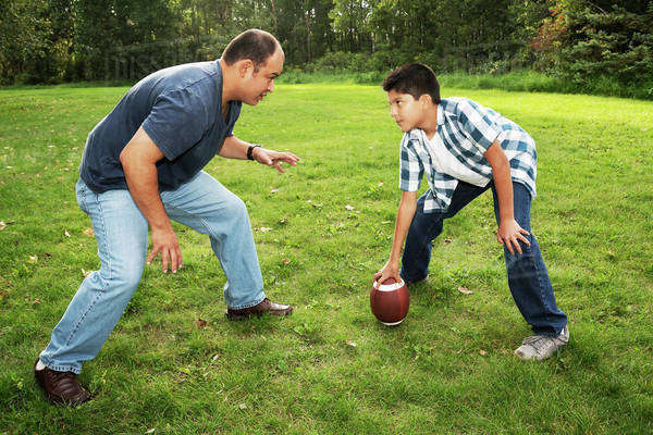 Father and son playing football in a park; Edmonton, Alberta, Canada Royalty-free stock photo