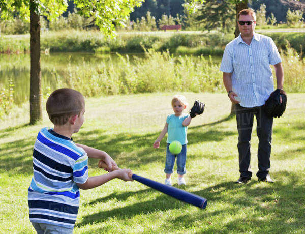 Father, son and daughter playing baseball in a park; Edmonton, Alberta, Canada Royalty-free stock photo