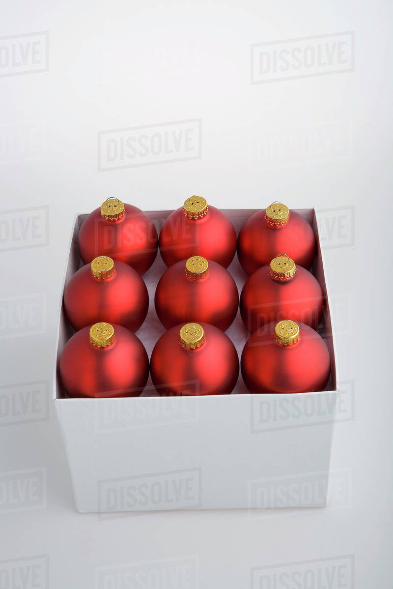 nine red christmas balls blurred in box on white background with green filter studio portrait