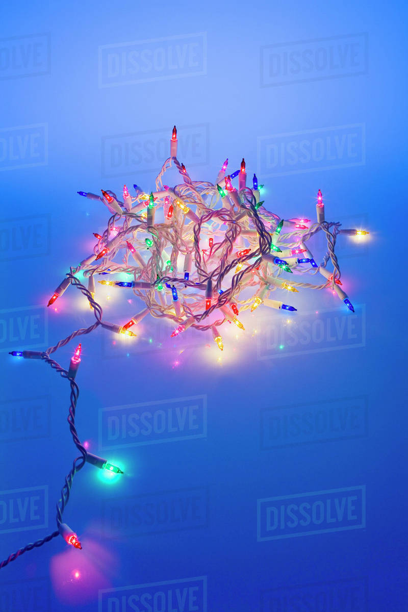 one strand of multi colored christmas tree lights coiled together with blue tint dark studio portrait