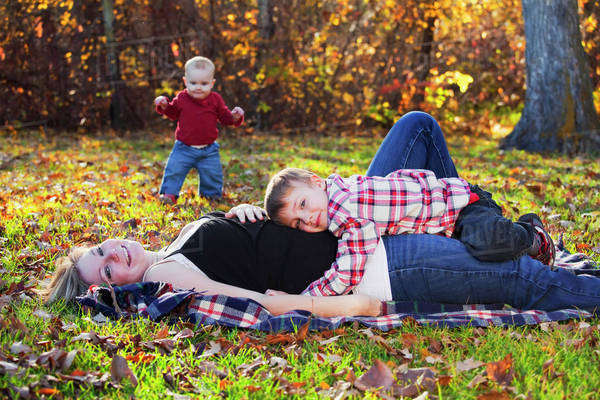 Mother, son and baby daughter play in a park in autumn;Edmonton, alberta, canada Royalty-free stock photo