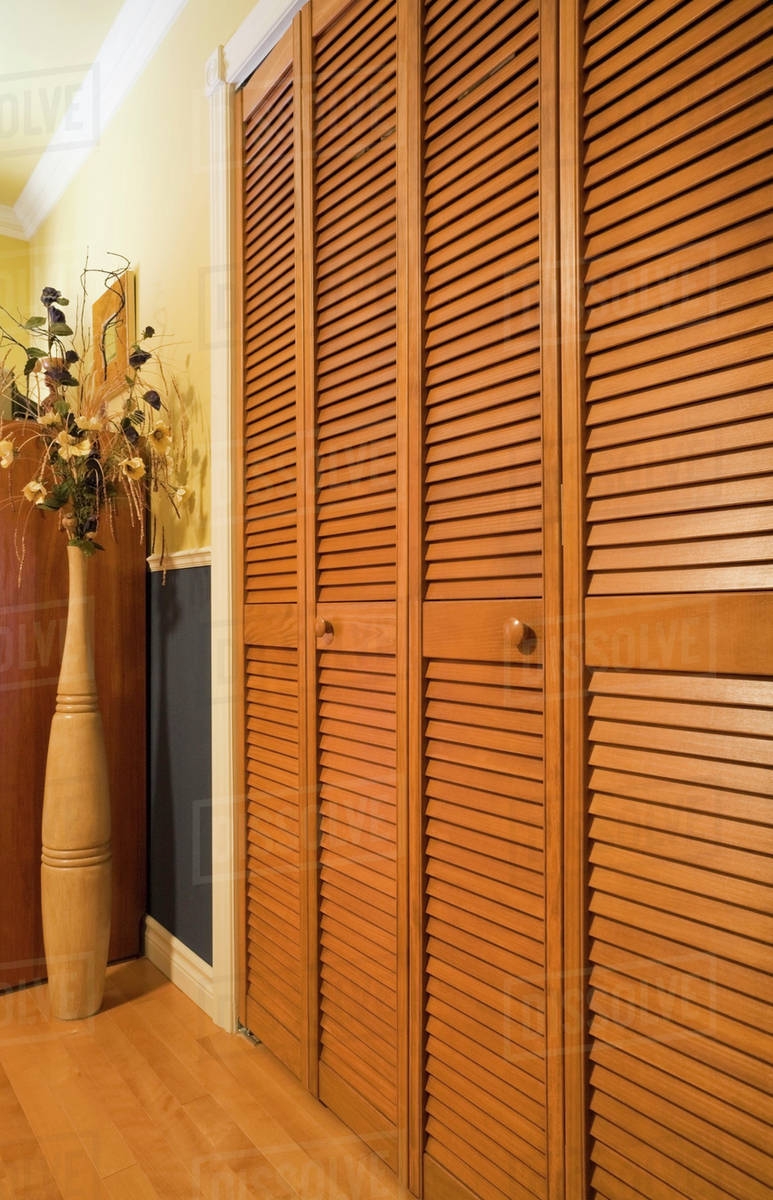 Louvered Panelled Wooden Closet Doors In A Bedroom Quebec Canada
