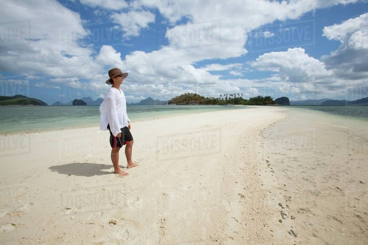 A Tourist Stands On The Pure White Sands Of Snake Island, Near El Nido
