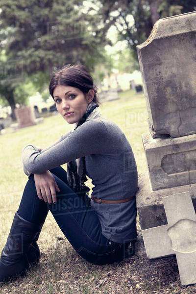 A Young Woman Sitting Against A Tombstone; Edmonton, Alberta, Canada Royalty-free stock photo