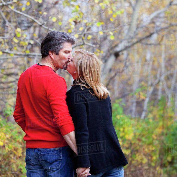 Husband And Wife Walking And Kissing In A Park In Autumn; St. Albert, Alberta, Canada Royalty-free stock photo