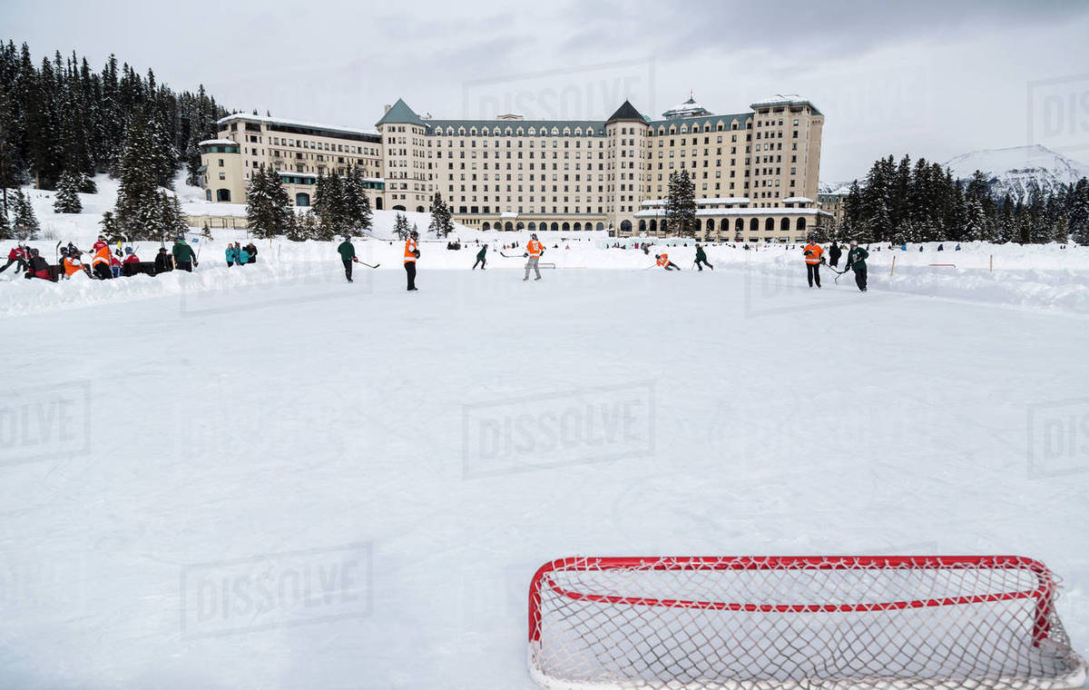 A View From Behind The Hockey Net During A Pond Hockey Game In The Winter On Frozen Lake Louise In Banff National Park Against The Background Of The Fairmont Chateau Lake Louise