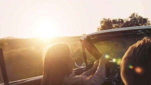 Close up of a couple driving classic cherry red convertible at sunset with sun flare. Steadicam shot. Royalty-free stock video