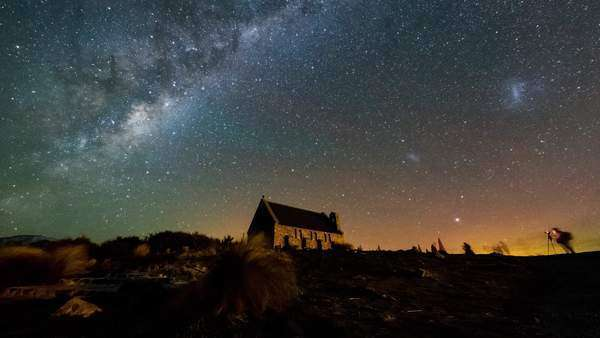 Mesmerizing scene of Aurora Australis (Southern Light) dancing behind Church of The Good Shepherd in Lake Tekapo, South Island with Magellanic Clouds and Milky Way rotating above. Timelapse pan right Royalty-free stock video