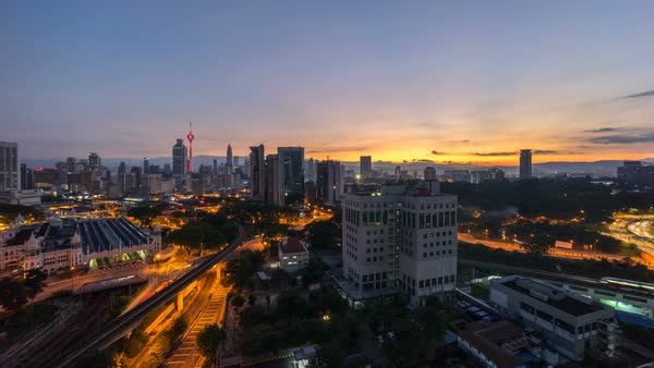 Beautiful sunrise of Kuala Lumpur city view from rooftop of a building with moving vehicle, clouds and sunlight burst Royalty-free stock video