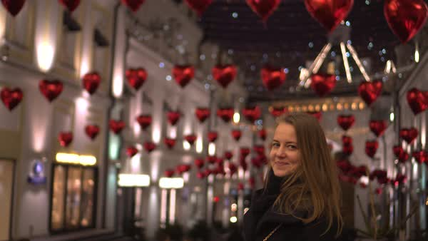 Pretty young woman smiles at decorated street on a St. Valentine's Day Royalty-free stock video