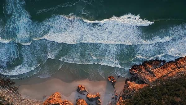 Ocean waves crashing onto coast, constant pattern of energy on coastline, aerial drone footage Royalty-free stock video