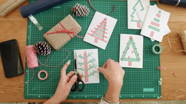Woman sitting on floor gift wrapping and writing christmas cards overhead christmas scene woman hands making xmas cards festive seasonal greeting gift tags royalty free m4hsunfo