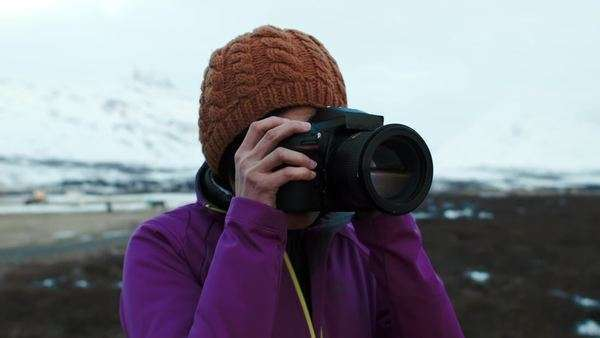 Adventurous travel woman taking photos on vacation in winter landscape Royalty-free stock video