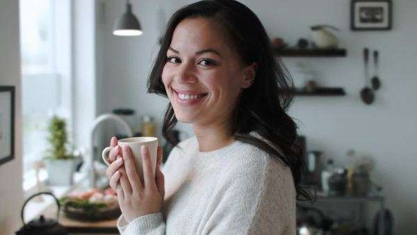 Smiling happy portrait of an attractive woman in her 20s holding a coffee tea mug in a stylish modern kitchen Royalty-free stock video