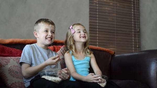 Brother and sister sit together and enjoy popcorn laughing at funny movie together Royalty-free stock video