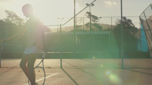 Determined teenage tennis player preparing to serve, slow motion with sun flare Royalty-free stock video
