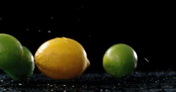 Fresh lemons and limes bounce and roll in slow motion across frame with slight pan on black background with water droplets splashing Royalty-free stock video