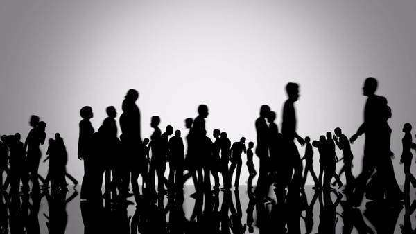 Silhouettes of a crowd of people walking on a reflective black surface past a bright background Royalty-free stock video
