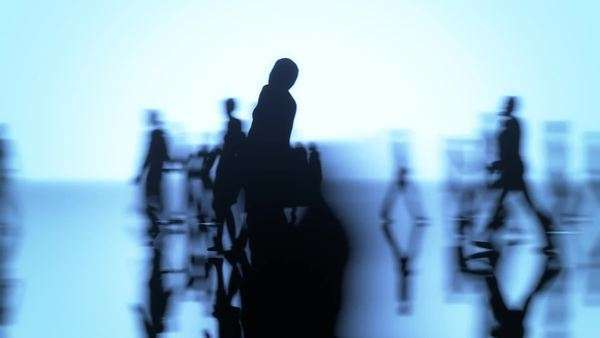 Silhouettes of a crowd of people walking on a reflective surface. Camera moving around one woman. Seamlessly loop. Royalty-free stock video