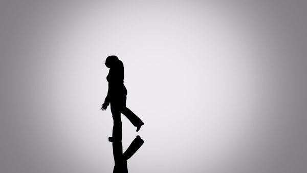 Silhouettes of a crowd of people walking on a reflective surface. Close up of one woman from crowd. Royalty-free stock video