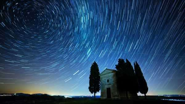 Lonely chapel and cypress trees in a field against night sky with startrails in Tuscany, Italy Royalty-free stock video