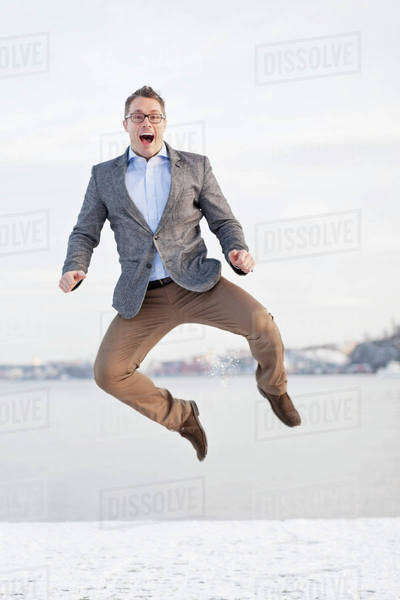 Excited mid adult man jumping in air Royalty-free stock photo