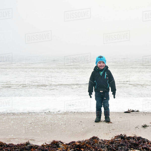 Smiling boy standing on beach having fun Royalty-free stock photo
